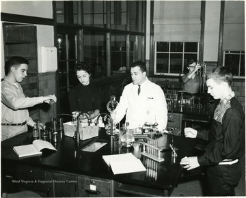 Teachers and pupils in University High School lab. At the time University High School was a division of West Virginia University for training teachers.  Pictured in the photograph are, from left to right:  Fred Truban, Carol Reynolds, Michael Caruso, and Scottie Riffle.  Girl in background unknown.