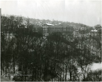 A view of Morgantown High School through trees in the winter.