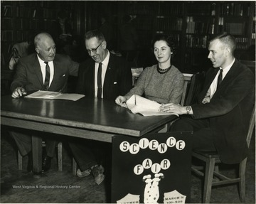 The people in the picture appear to be science fair officals or judges. From left to right, Scott H. Davis, Carroll Palmer, Betty Alamong, and John Bensenhaver.