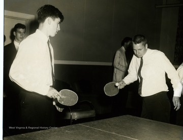 Two male students, Bill Gainer 'left' and Rick Defere 'right' are playing table tennis at the triad graduation festival. Dave Smith is watching in the background 'far left'.