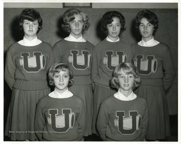 University High School cheerleaders pose for a group portrait. Back row, far right, Sharon Wolfe; Front row right to left are Tina Thomas and Thomasene Cook.