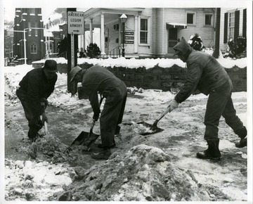 Three road crew members are shoveling a snowy sidewalk.