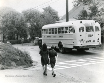 Two girls approach Monongalia County school bus Number 34 on Collins Ferry Road.