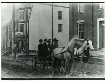 Two horses are pulling a wagon with three ladies and a gentleman down Pleasant Street in Morgantown, West Virginia.