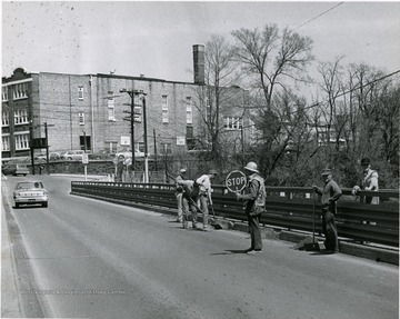 Men at work repairing Walnut Street Bridge. Morgantown Junior High School visible in the background.