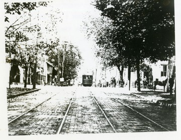 A streetcar is driving on High Street at the corner of High and Pleasant Street. Moore and Parriott's Drug Store is on the right side on the corner.
