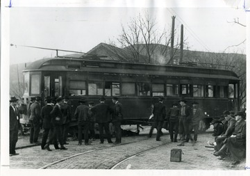 Passengers are standing in front of the Sabraton Streetcar which has derailed in Morgantown, West Virginia.