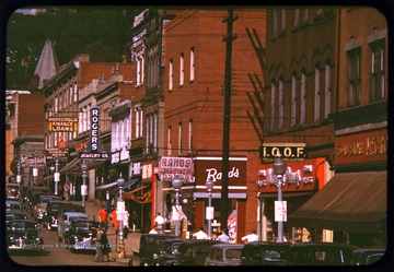 A view of High Street, looking north, in downtown Morgantown.  This view features automobiles and pedestrians during a busy time of day.  Shop signs are clearly in view, including Rands Drugs, Rogers Jewelry Company, and Comuntzis Restaurant.