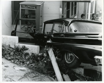 Two people are standing behind an automobile that wrecked near Jimmy's Campus Lunch on North High Street in Morgantown, West Virginia.