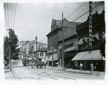 A horse and buggy and a streetcar are driving down High Street near Hirschmans Store. They are near the intersection of Walnut and High Street in Morgantown, West Virginia.