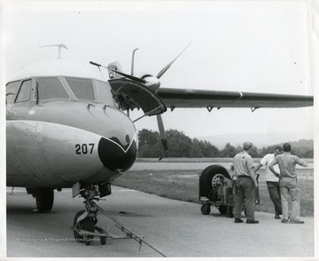 Three airport employees stand next to a Nord N262 airplane at the Morgantown Municipal Airport.