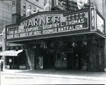 The front enterance of the Warner Theatre. The movie 'The Blonde Captive' is advertised on the marquee.
