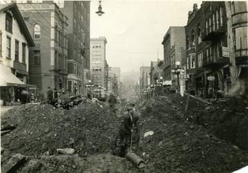 A view looking North of men excavating High Street for new pipelines.