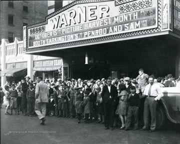 A group of children in front of the Warner Theatre on High Street.  Marquee reads, 'October is 'Picture Harvest Month' and 'Booth Talkington's 'Penrod and Sam.'