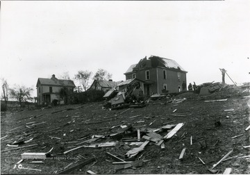 An area damaged by a windstorm. The roof of the house in the center has been torn apart, and in the front, a car is flipped upside down.