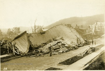 Building destroyed during a windstorm.  Roof of building is on the street.