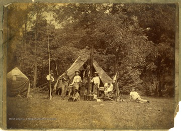View of assorted men, musical instruments, and guns in a camp setting, Morgantown W. Va.