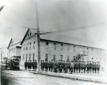 World War I trainees at attention in front of barracks.