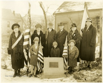 Standing L to R: Mrs. R. H.  Edmondson, Mrs. George C. Baker, Thornton Kerns (holding Michael Kerns' boardax), Dr. W. C. Kelly, Mrs. W. E. Price, Mrs. John L. Johnston, in front children of Charles O. Koontz, descendants of Micheal Kerns.' The marker is located at 305 Dewey Street in Morgantown.