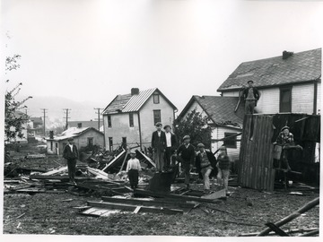 Children standing on the debris from a windstorm.