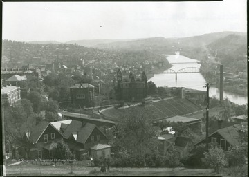 Stadium and Woodburn Hall are in the foreground and the River Bridge over the Monongahela River is in the background.