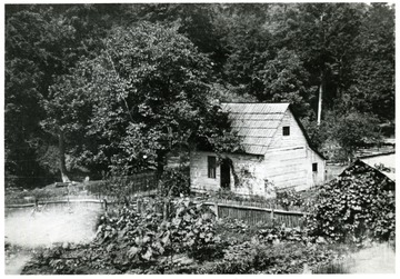'House has wood shingles.  Original photo owned by Clyde Moneypenny who was born here in 1884. - still living today, August 25, 1977.'