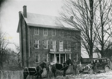 Two men standing in front of the home, each with a horse, and two women standing in front of a car with a pet dog.