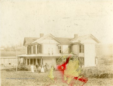 'Dwyer Home in Rader Valley'. Portrait of family standing along the front of their home. Two young girls pose for the picture while standing on the porch roof.