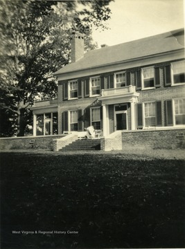View of the Tuscawella Home in Lewisburg, West Virginia. A person sits outside on a bench reading a newspaper.