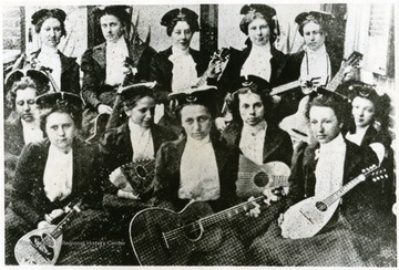 Group portrait of female members of a Mandolin and Guitar Club with their instruments.