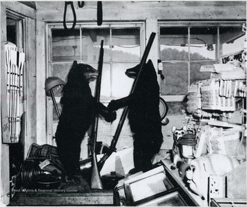 Two stuffed bears holding rifles in Whites County Store, Neola, Greenbrier County.  Photo from 1968 Christmas Calendar, Scenes taken from the Greenbrier Valley in 1968, Printed by the Fairlea Print Shop Inc.<br /><br />