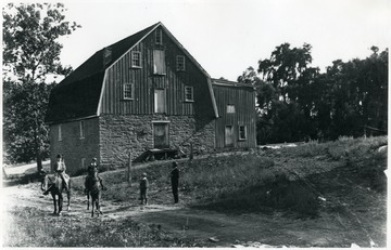 View of a large stone barn building next to a road and men on horseback at Ft. Spring.