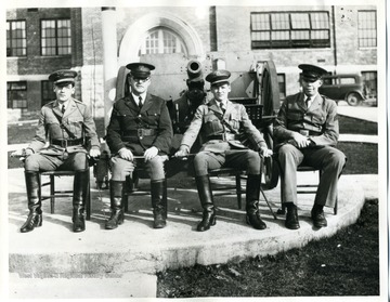 Group portrait of uniformed men with sabers drawn pose in front of Greenbrier Military School.