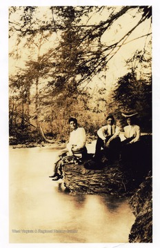 View of Maude Sennett and two others sitting on the edge of a rock forming the bank of a river in Morgantown.