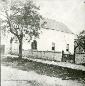View of the Old Episcopal Church, now the Asbury Methodist Church, and a wall surrounding the old Episcopal graveyard.