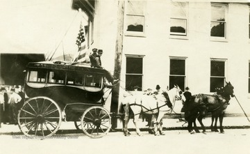 A horse-drawn carriage stops at West 2nd Street alongside the Bailey House.