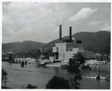 'The new 400,000 kilowatt Kanawha River Plant of Appalachian Electric Power Company at Glasgow, West Virginia, as it appears from the river side. The first of two 200,000 kilowatt units is now in service. The second unit is scheduled for completion late this fall.'