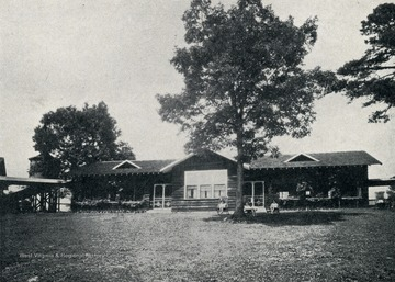 Tuberculosis patients are seated in front of a cottage at the Hillcrest Sanitarium.