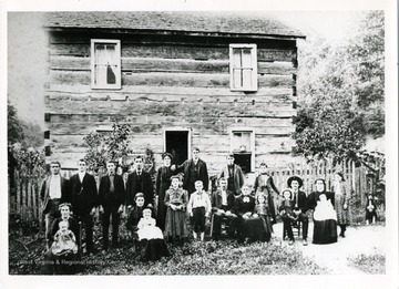A group portrait in front of the James W. Moneypenny family home in Lewis County, West Virginia. From left to right: 'Levi Smith, husband of Bertie; Harvey C., a son; George, a son; Allen Markley, husband of Mary Luverna; Bertie, daughter; James F., a son; Jacob, a son; Eliza A., daughter; Sherman, son sitting, holding his son William; Luella, wife of Sherman, holding their daughter Anna. Front Row: left to right: sitting Ella May, wife of Harvery Columbus, holding their daughter Rosa; sitting Luverna, daughter, wife of Allen, holding their daughter Sallie; Bessie, daughter; Albert, son; James William Moneypenny, the father and grandfather; Sarah Ann Conley Moneypenny, wife of James W.,; Flora, daughter.'