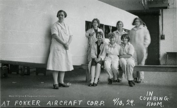 A group of women workers sitting on a bench and standing by their project at the Fokker Aircraft Corp.