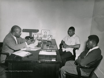 Two young African American men sit in an administrative office at the West Virginia Industrial School for Colored Boys in Lakin.