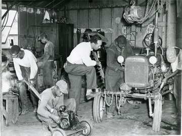 Group of boys at the West Virginia Industrial School for Colored Boys and their instructor work on fixing an automobile and a lawnmower together.