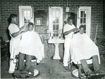 Two young African American boys get their haircuts at the West Virginia Industrial School for Colored Boys.