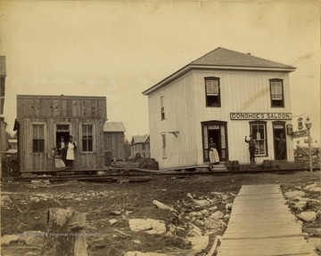 A view of Donohoe's Saloon in Tucker County. A residence is seen to the left of the saloon and people are standing outside on both porches.