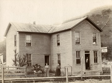 View of the Hotel W. H. Shobe in Laneville, West Virginia. Two women stand outside and a man stands in the entrance way.