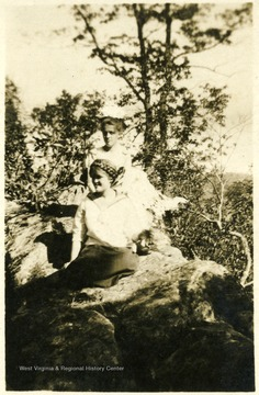 Photograph of Maggie and Helen Ballard sitting on rocks on a postcard.