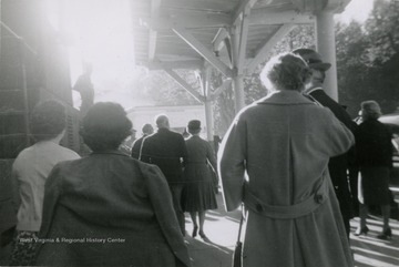 People gather for Dwight D. Eisenhower's visit to Hot Springs.  Ike and Mamie Eisenhower walking away from camera in distance in center of photo.