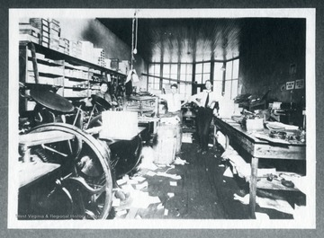 Three employees and paper scattered on the floor of W. W. Logan's Print Shop.