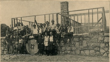 Young people seated on the foundation of the Lewis County Cottage under construction at Jackson's Mill 4-H Camp.