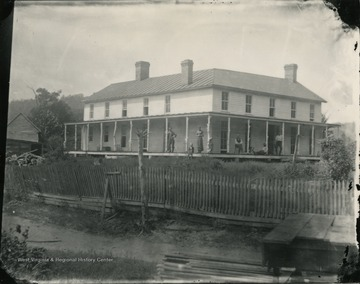 A view of a residence enclosed by a wooden fence at Jackson's Mill with people sitting and standing on the porch.